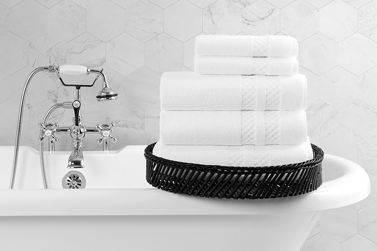 A stack of folded Capitol Bath Towels and Wash Cloths rest on the edge of an classic style clawfoot bath tub.