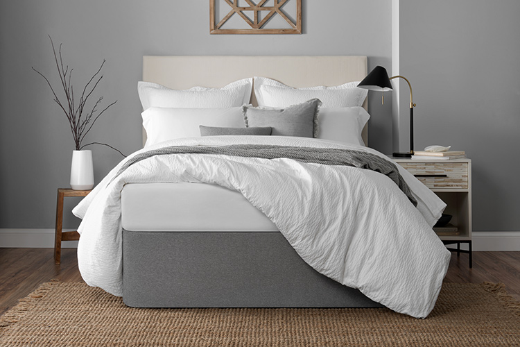 A well-made hotel bed, the duvet pulled up over one corner to showcase a graphite colored Circa Bed Wrap.