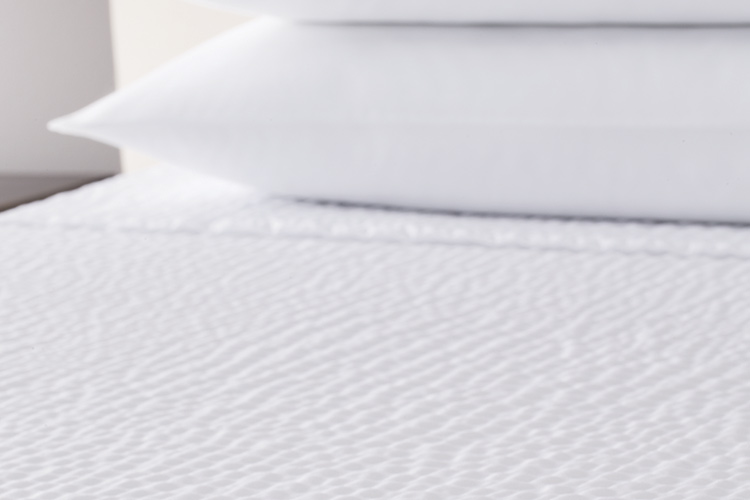 A detail shot of a bed featuring a Cumulus top cover.