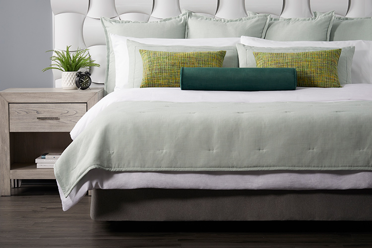 A well-made hotel bed featuring two Limelight throw pillows and a Eucalyptus bolster pillow.