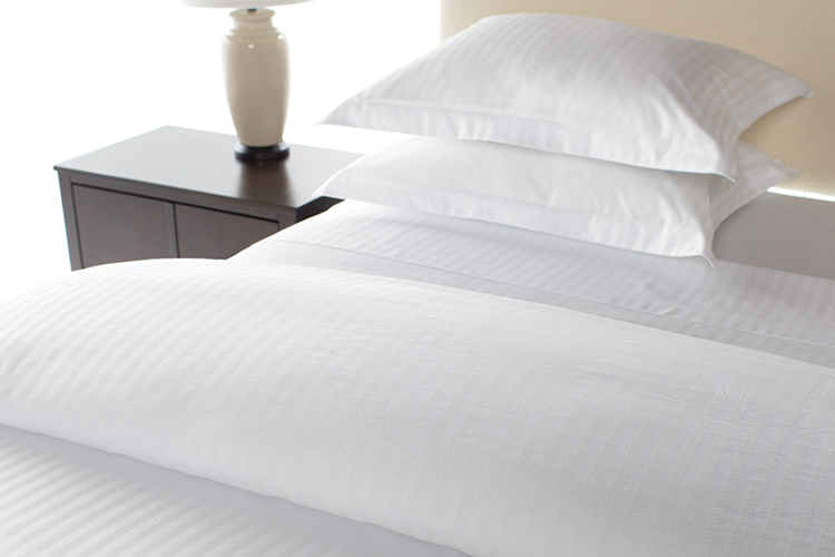 A detail shot of a hotel bed featuring our Designer Closure Duvet Cover.