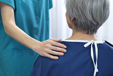 A nurse's hand rests on a patient's shoulder.