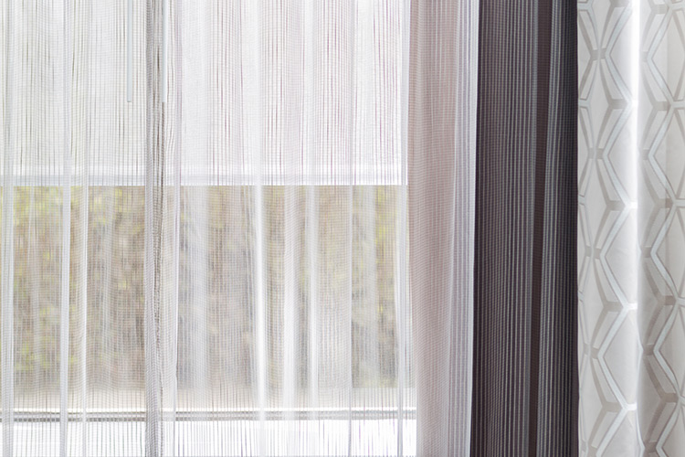 A detail shot of a window featuring a Dynamo window sheer and portier drapery.