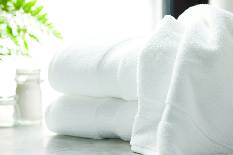 A Lynova bath towel draped over a stack of two folded Lynova bath towels.
