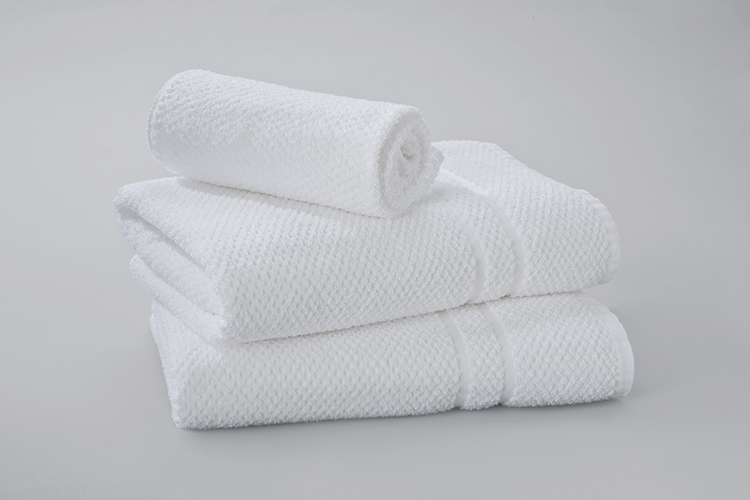 A rolled Pique Weave wash towel rests atop a stack of two folded Pique Weave bath towels.