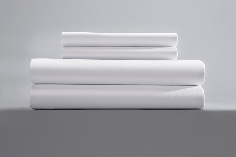 a stack of two pillowcases and two sheets for motels in single pick percale