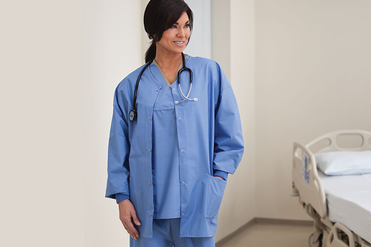 A woman standing in a patient room, wearing blue scrubs and a a warm-up jacket.