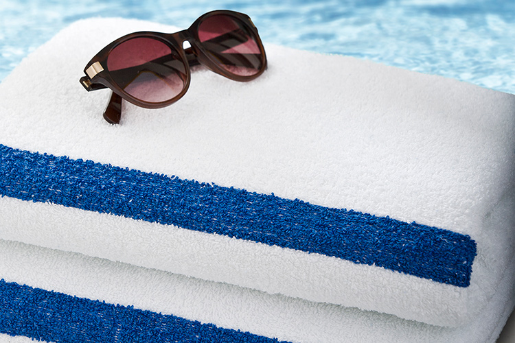 A pair of sunglasses sits atop a stack of two classic Stripe Pool Towels.