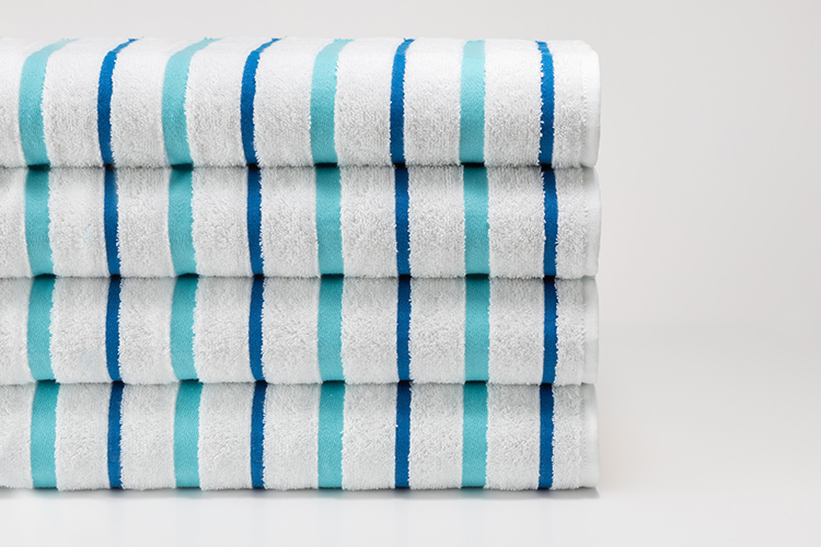 A folded stack of Seaglass Stripe Pool Towels.