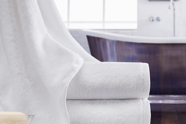 A Vidori towel draped delicately over a stack of two folded Vidori bath towels.