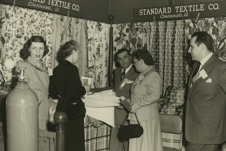 A vintage photo of Standard Textile employees standing in a fabric showroom.