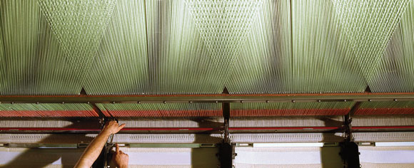 An abstract angle showing a fabric weaving machine, dozens of threads fan out from various points on the machine.