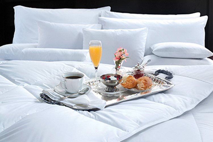 A silver tray of various breakfast foods rests on a well-made hotel bed.