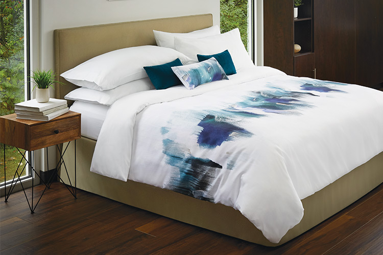 A fully made hotel bed featuring decorative pillows and a custom printed duvet cover.