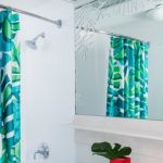 A hotel bathroom featuring a vibrant blue and green shower curtain.