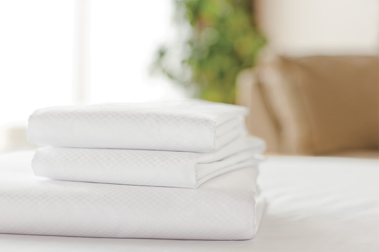 A stack of folded white Centium Satin sheets rest on a bed.