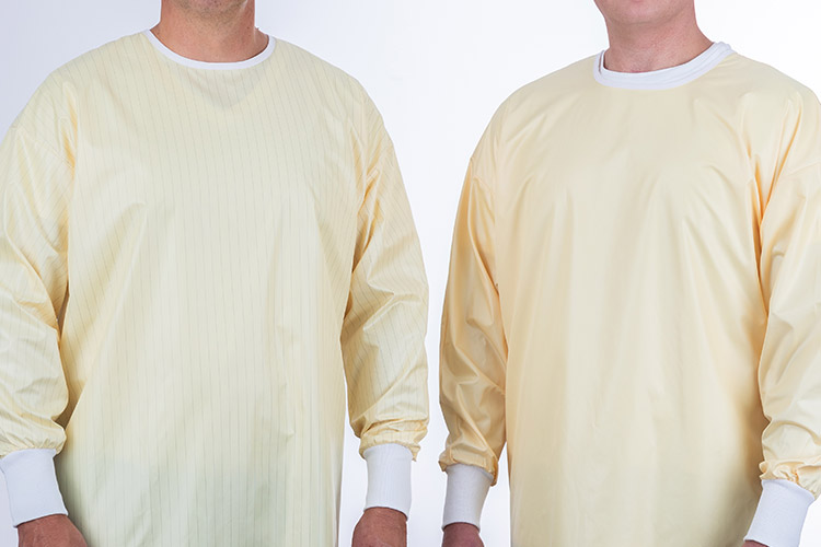 Two people wearing isolation gowns.