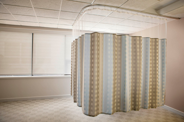 A small area of a hospital room sectioned off with privacy curtains.